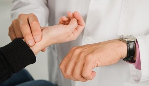 Доктор измеряет пульс у пациента