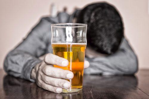 Стакан пива в руках спящего за столом