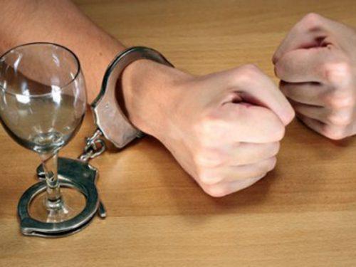 Рука, прикованая наручником к рюмке