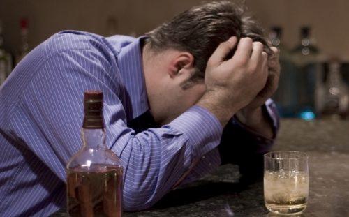 Пьяный человек спит за столом